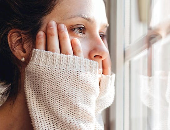 A woman looking out a window with her hands on either side of her face