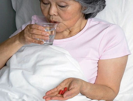 Femme plus âgée assise dans son lit en prenant des médicaments