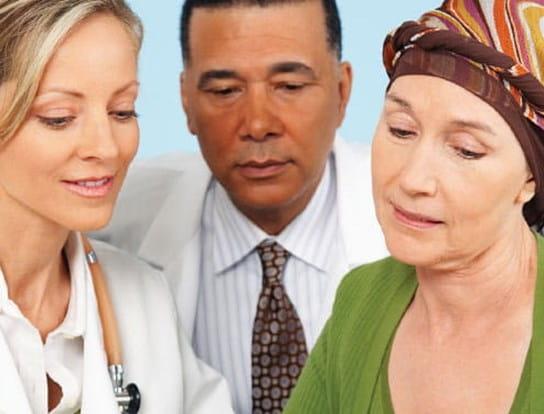 Une femme atteinte de cancer discutant avec un homme et une femme qui portent des blouses blanches