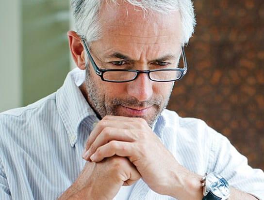 Un homme qui a les cheveux gris et qui porte des lunettes jouant aux échecs