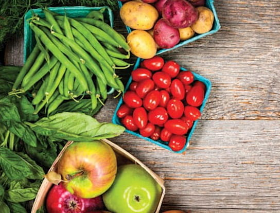 Des pommes, des tomates, des fèves vertes et un oignon sur une table