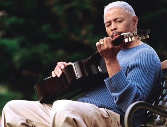 Un homme assis sur un banc de parc en train de jouer de la guitare