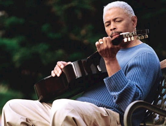 A man sitting on a park bench, playing a guitar