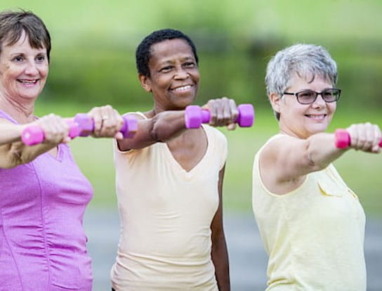 Three women standing next to each other and exercising with dumbbells
