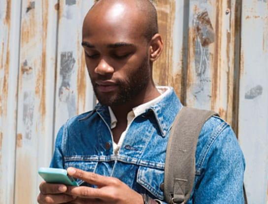 Un homme, un sac à dos sur l'épaule, regardant son téléphone cellulaire
