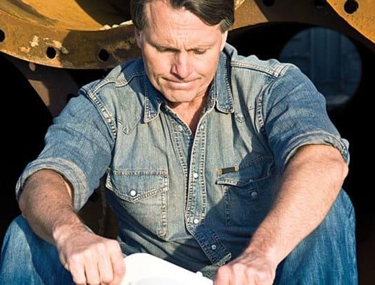 Un travailleur de la construction assis près de la machinerie