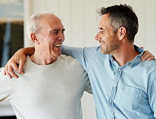 Two men smiling with their arms around each other shoulders