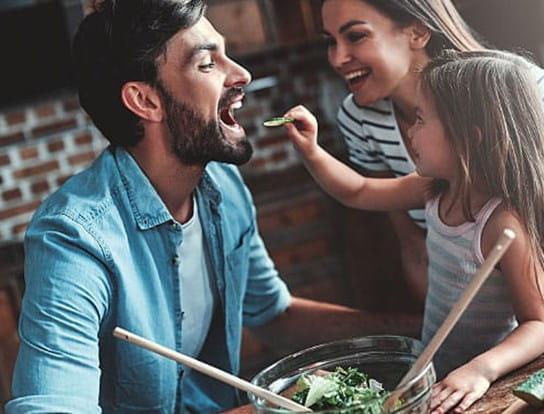 Petite fille plaçant un bout de laitue dans la bouche de son père pendant que sa maman les regarde en riant.