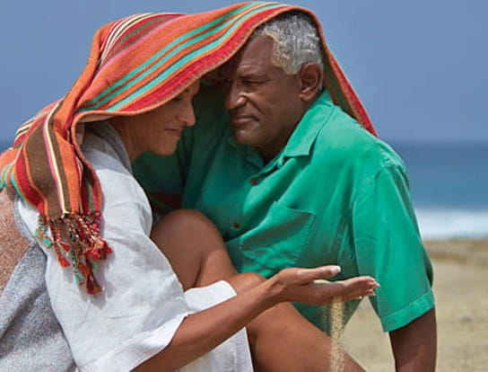 An older couple hugging under a towel at the beach