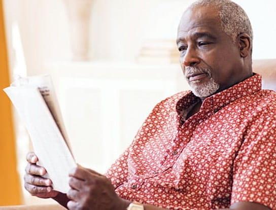 Un homme âgé assis sur une chaise, en train de lire le journal
