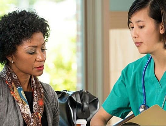 Femme à qui son médecin montre un graphique.