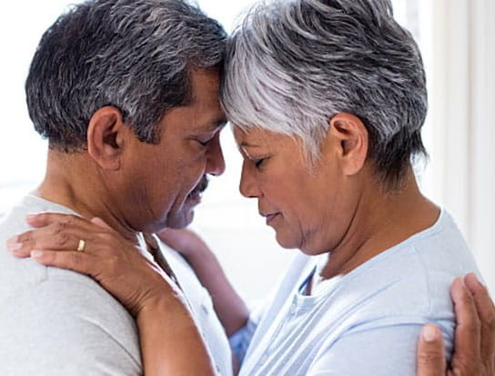 An older man and woman hold each other closely their foreheads touching