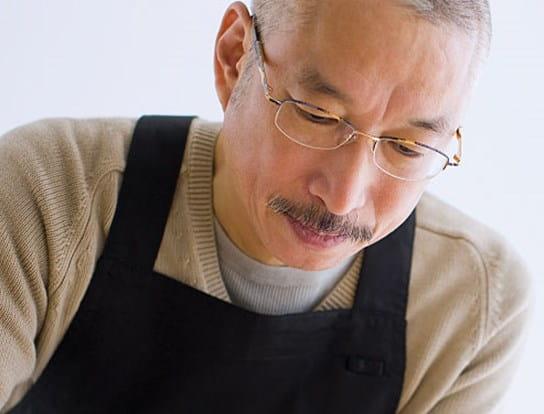 Un homme grisonnant, portant des lunettes, en train de travailler le bois