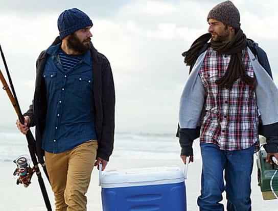 Deux hommes marchant sur la plage en tenant des lignes à pêche