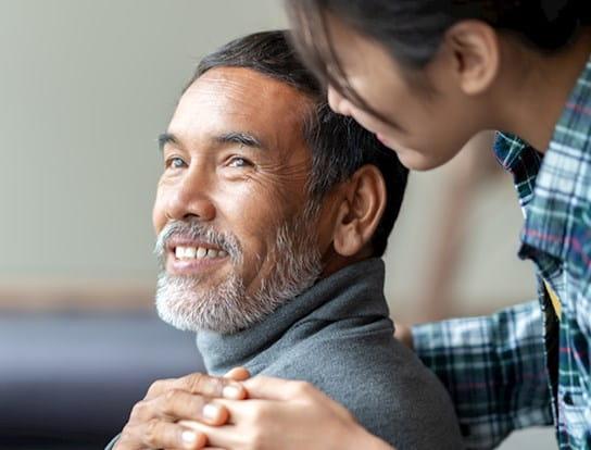 Un homme sourit et une femme se tient derrière lui, la main posée sur son épaule.