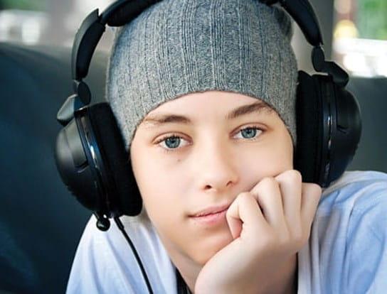 Un adolescent porte des écouteurs, en position assise et le menton reposant dans sa main.