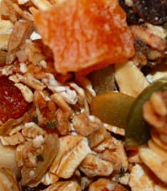 Plan rapproché d'un bol de céréales granola avec fruits et noix.