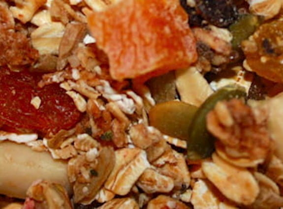 A close up on a bowl of granola with fruit and nuts