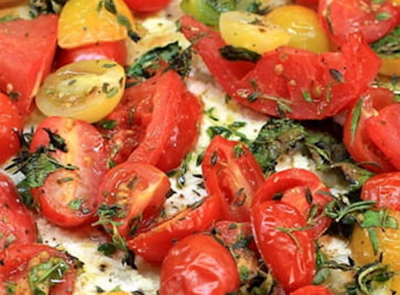 A close up image of a phyllo tart with tomatoes on it