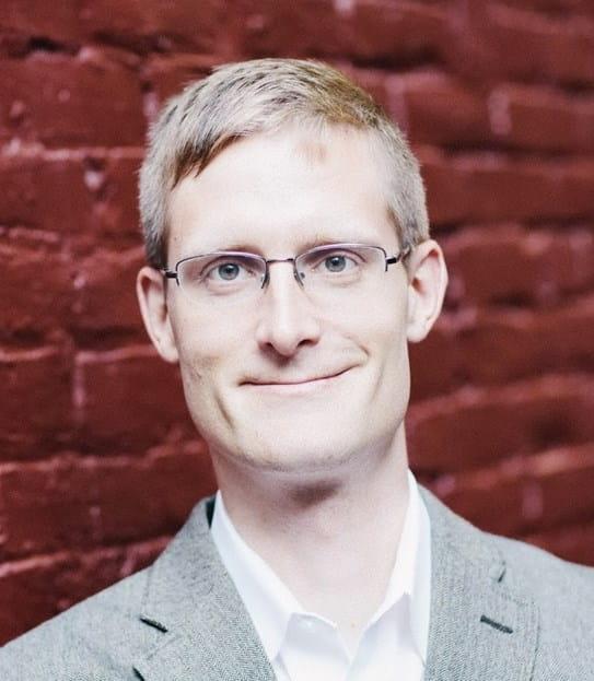 Paul Toren souriant, un mur de briques en arrière-plan.