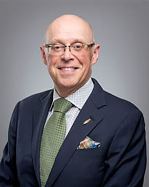 A bald man wearing eyeglasses smiling for the camera