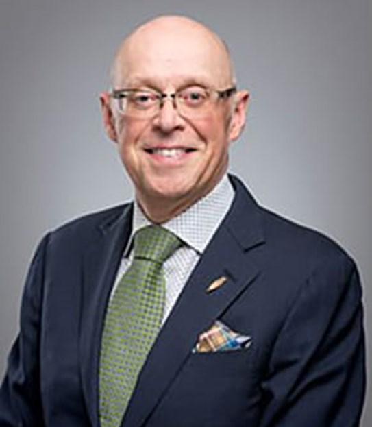 Un homme chauve portant des lunettes qui sourit pour la caméra.
