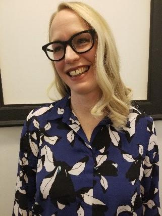 Une femme portant des lunettes qui sourit.