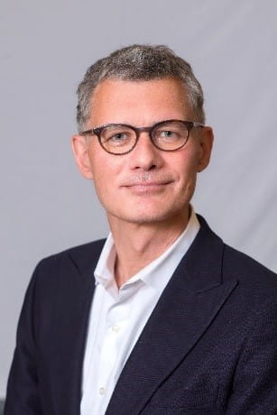 A man with greying hair and wearing eyeglasses looking at the camera