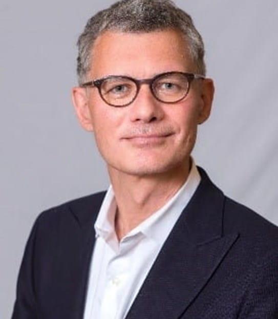 Un homme grisonnant portant des lunettes qui regarde une caméra.
