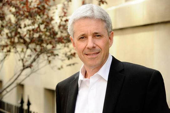 A close up of a grey haired man in a suit standing in front of a building