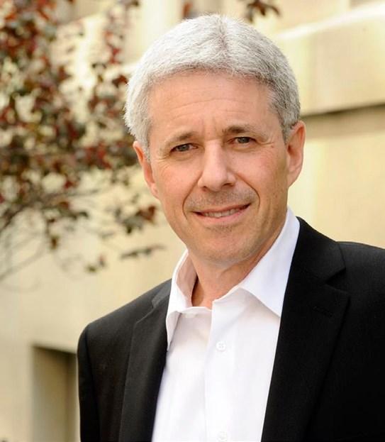 Un gros plan d'un homme aux cheveux gris en complet, devant un édifice.