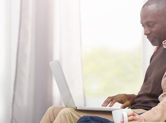 A man and woman sitting together and looking at a laptop.