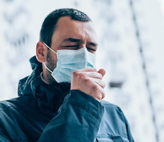 Man wearing a face mask and coughing.