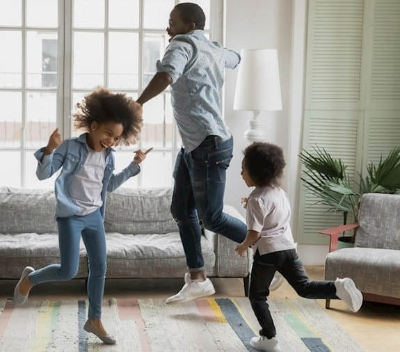 A father and his two daughters dance in their living room