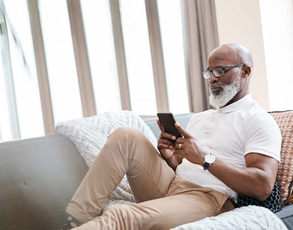 An elderly man sits on his couch looking at his phone