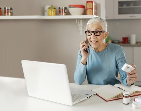 Une femme sur un téléphone tenant des médicaments