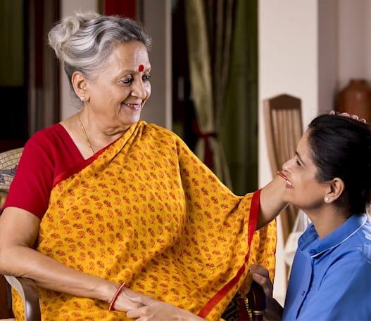 Une femme âgée assise, souriant à une femme plus jeune qui la regarde