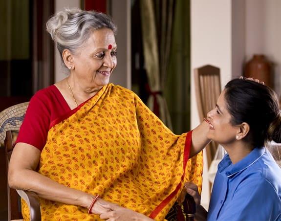 Femme plus jeune et femme plus âgée souriant en s'enlaçant.