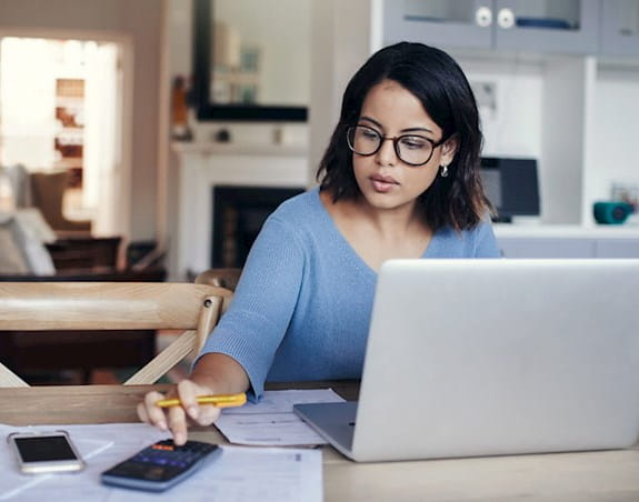 A woman is sitting in front of a laptop and using a calculator