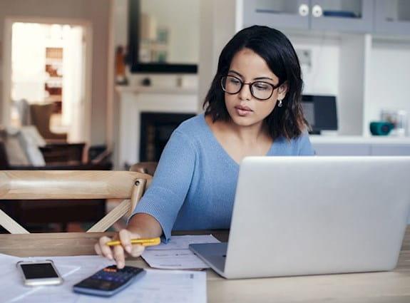 Femme assise devant un ordinateur portable, utilisant une calculatrice.