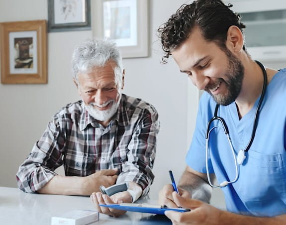 A doctor and his patient are smiling together while the doctor takes notes