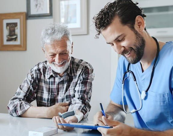 Médecin et son patient souriant pendant que le médecin prend des notes.