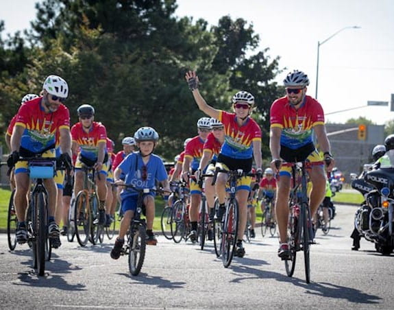 A child on a bicycle leads a group of 10 cyclists wearing matching uniforms