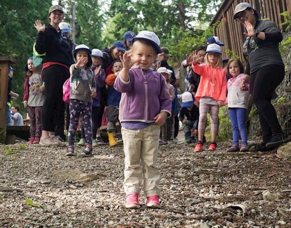 Une petite fille debout face à un groupe d'adultes et d'enfants