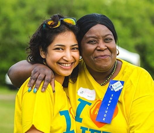 Une femme portant un insigne de survivant posant avec une autre fille portant un t-shirt Relais pour la vie.