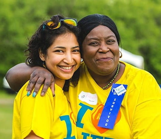 A woman wearing a survivor badge posing with another girl in a Relay For Life t-shirt.