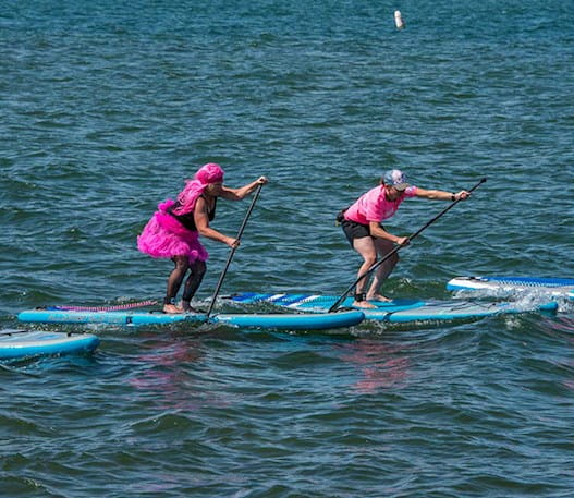Four people on paddle boards in water wearing pink outfits