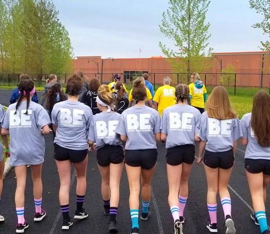 Un groupe de jeunes filles portant un t-shirt du Relais pour la vie (de dos).