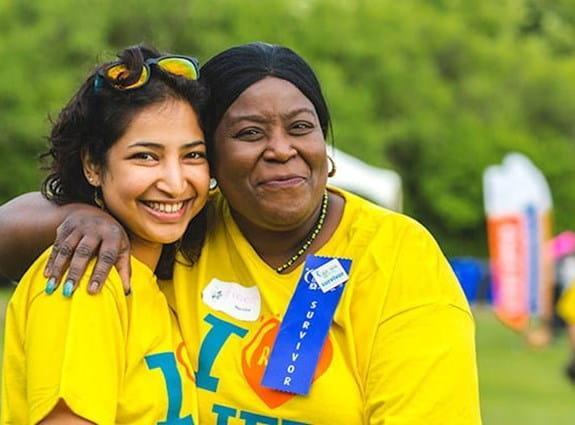 Une femme portant un insigne de survivant près d'une jeune fille portant un t shirt du Relais pour la vie