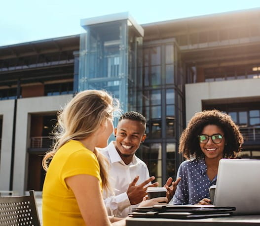 Quatre personnes assises à l'extérieur et travaillant en se sourient les unes aux autres.